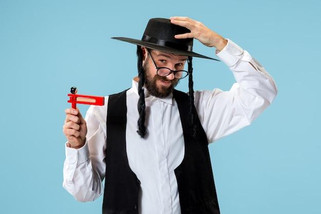 Portret van een jonge orthodoxe joodse man met houten gragerratel tijdens festival purim. vakantie, feest, jodendom, traditie, religie concept.