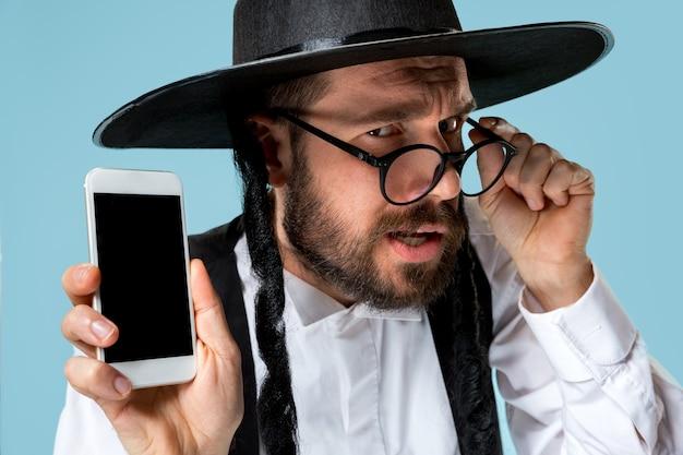 Portret van een jonge orthodoxe joodse man met mobiele telefoon in de studio.