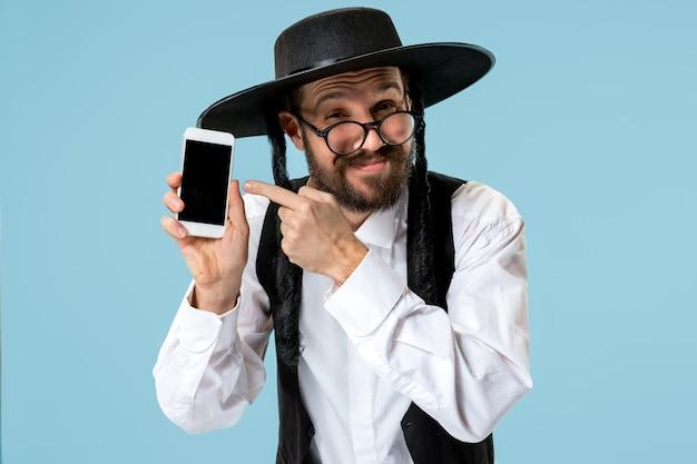 Portret van een jonge orthodoxe joodse man met mobiele telefoon in de studio