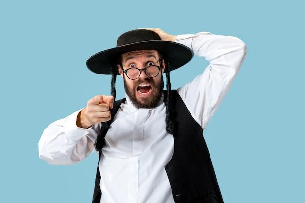 Portret van een jonge orthodoxe joodse man tijdens festival purim. vakantie, feest, jodendom, religie concept. menselijke emoties