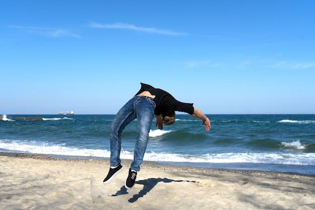 Portret van een jonge parkour-man die flip of salto op het strand doet. bevroren moment van omdraaien.