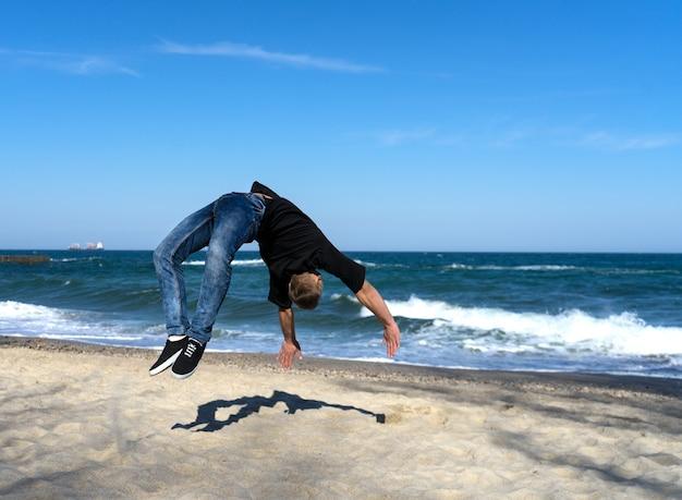 Portret van een jonge parkour-man die flip of salto op het strand doet