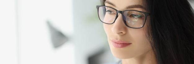 Portret van een jonge peinzende zakenvrouw met een bril die uit het raam kijkt