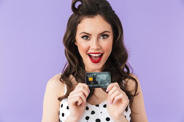 Portret van een jonge pin-up vrouw in vintage polka dot jurk die lacht terwijl ze een plastic creditcard vasthoudt die over een violette muur wordt geïsoleerd