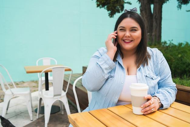 Portret van een jonge plus size vrouw die aan de telefoon praat terwijl ze buiten in de coffeeshop zit.