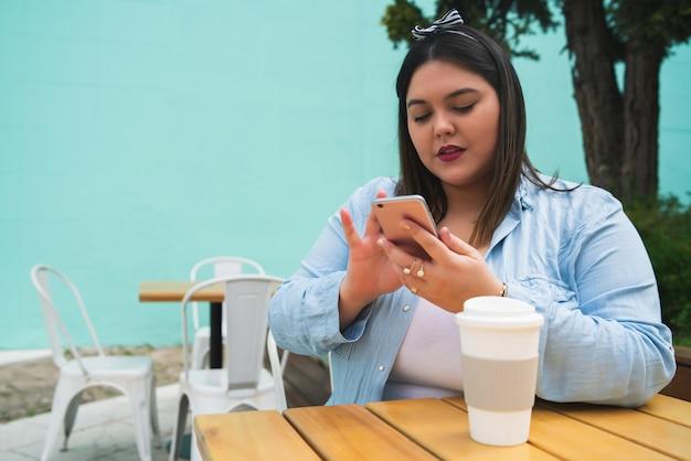 Portret van een jonge plus size vrouw die haar mobiele telefoon gebruikt terwijl ze in de coffeeshop zit. communicatie en technologie concept.