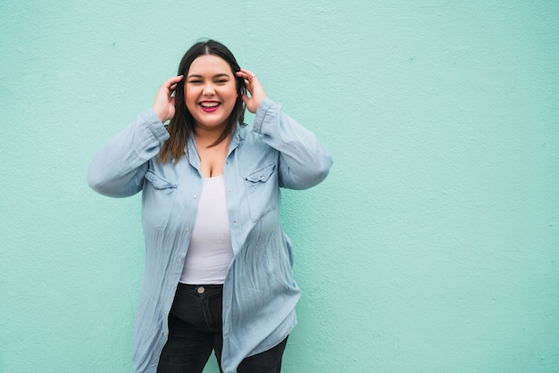 Portret van een jonge plus size vrouw die lacht terwijl ze buiten tegen een lichtblauwe muur staat.