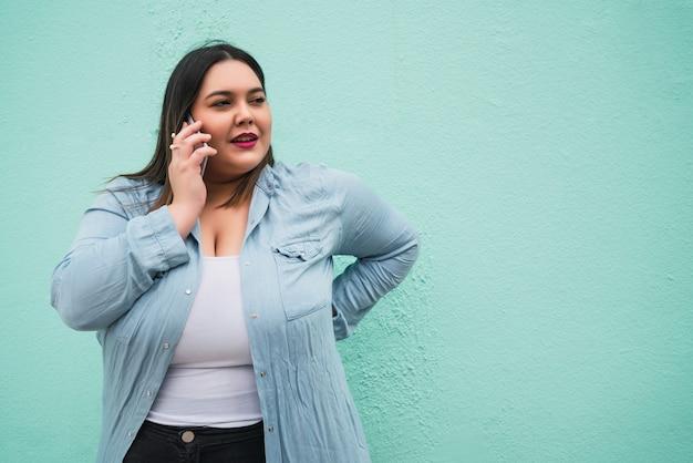 Portret van een jonge plus size vrouw die lacht terwijl ze buiten telefoneert tegen een lichtblauwe muur. communicatieconcept.