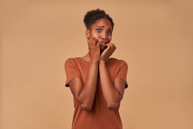Portret van een jonge pop-eyed donkere huid krullend vrouw die bang handen opheft naar haar gezicht en grijnzend gezicht terwijl ze angstaanjagend kijkt, geïsoleerd op beige