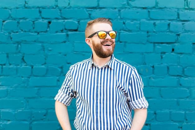 Portret van een jonge positieve stijlvolle lachende man met een snor en baard tegen de achtergrond van