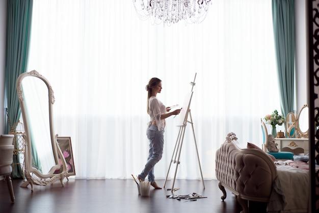 Portret van een jonge pragnant vrouw die met olieverven op wit canvas, zijaanzichtportret schildert