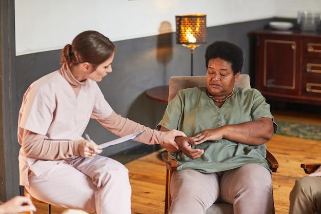 Portret van een jonge professional in de geestelijke gezondheidszorg die tijdens de therapiesessie met een oudere vrouw praat