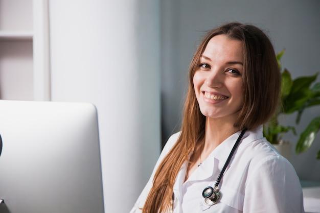 Portret van een jonge professionele vrouwelijke arts die bij kliniek glimlacht. close-up van een medicijnmateriaal in het ziekenhuis