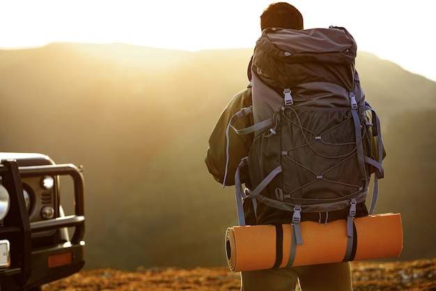 Portret van een jonge reizigersmens in wandeluitrusting die zich bij dageraad dichtbij zijn off-road auto bevindt