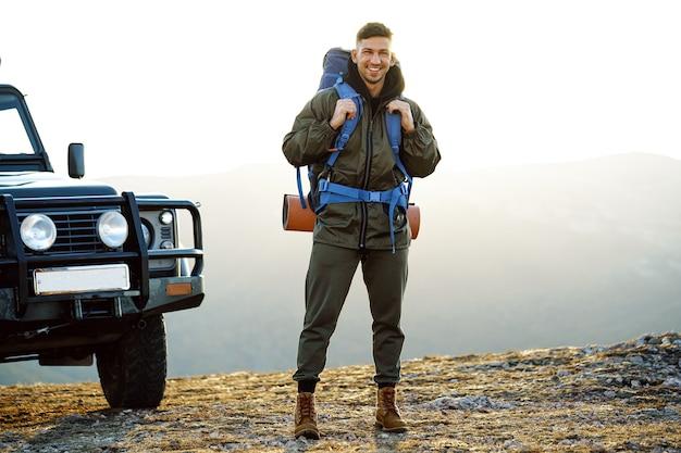 Portret van een jonge reizigersmens in wandeluitrusting die zich dichtbij zijn off-road auto bevindt
