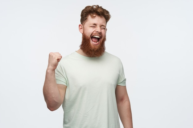 Portret van een jonge roodharige bebaarde man draagt een leeg t-shirt, steekt zijn vuist op en schreeuwt tijdens het kijken naar een voetbalwedstrijd.