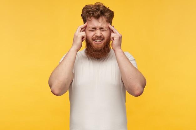 Portret van een jonge roodharige man met een grote baard, houd hallo vingers op de tempel, sloot hallo ogen