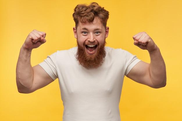 Portret van een jonge roodharige vrolijke man met een zware baard, glimlacht breed en toont zijn spieren