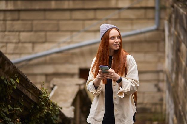 Portret van een jonge roodharige vrouw die in de stad loopt en een smartphone gebruikt, een knappe vrouwelijke reizigersbro...