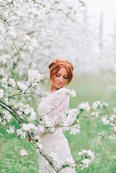 Portret van een jonge roodharige vrouw in een bloeiende appelboomgaard