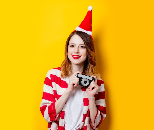 Portret van een jonge roodharige vrouw in kerstman hoed en gestreept shirt met klassieke camera op gele achtergrond. kersttijd