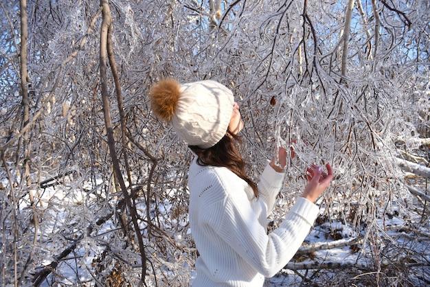 Portret van een jonge russische vrouw in witte trui en muts naast bevroren takken van berkenbomen