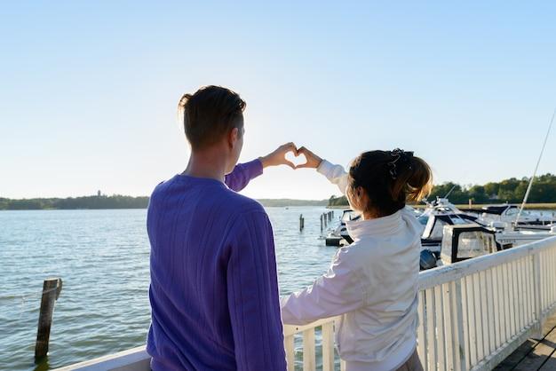 Portret van een jonge scandinavische man en jonge aziatische vrouw als multi-etnisch koppel samen en verliefd op de pier buiten