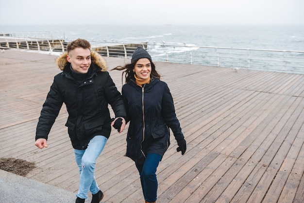 Portret van een jonge schattige liefdevolle paar wandelen op het strand buiten plezier.