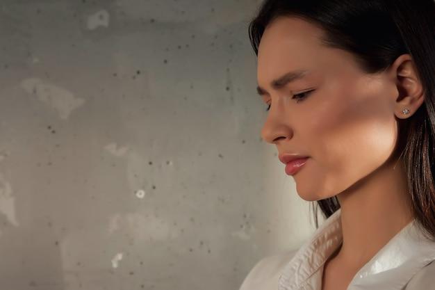 Portret van een jonge, schattige, vrolijke vrouw in een wit overhemd die wegkijkt over de achtergrond van een oude muur met schaduw van gebladerte. reclameconcept van gezonde levensstijl en zelfzorg. ruimte kopiëren voor site of spa