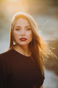 Portret van een jonge sensuele vrouw op een zonsondergang