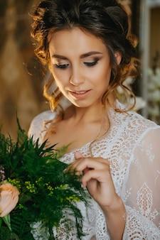 Portret van een jonge sexy bruid in een witte kanten negligé in het hotel