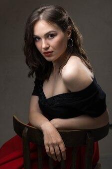 Portret van een jonge sexy brunette meisje in een kanten top in dramatische tinten. oude foto.