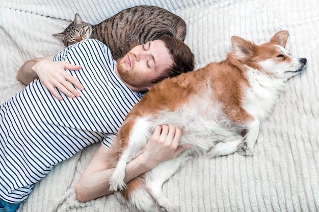 Portret van een jonge slapende man met zijn hond en kat op het bed