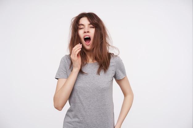 Portret van een jonge slaperige bruinharige vrouw gekleed in een basic grijs t-shirt met hand naar haar mond terwijl geeuwt met gesloten ogen, geïsoleerd op wit