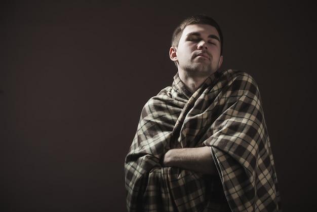 Portret van een jonge slaperige man gehuld in een plaid. concept van een harde ochtend ontwaken en werkstemming