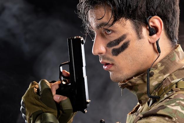 Portret van een jonge soldaat in camouflage die een pistool op de zwarte muur houdt