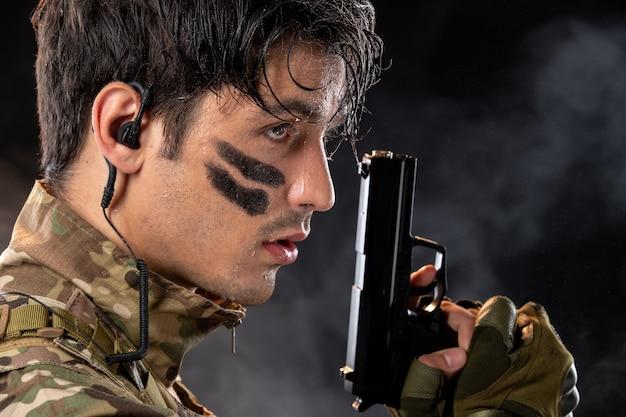 Portret van een jonge soldaat in camouflage die een pistool op zwarte muur richt