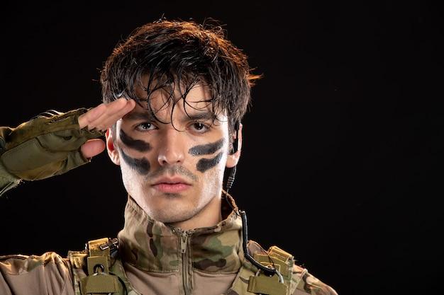 Portret van een jonge soldaat in camouflage die op zwarte muur salueert