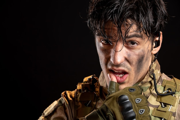 Portret van een jonge soldaat in uniform op de donkere muur