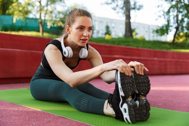 Portret van een jonge sportieve vrouw die een trainingspak draagt en haar lichaam uitrekt op een fitnessmat tijdens de training in het groene park