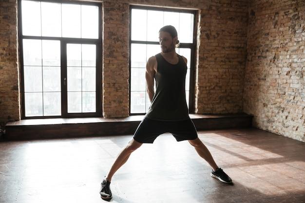 Portret van een jonge sportman die bij de gymnastiek uitwerkt