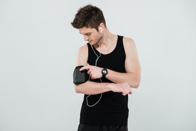 Portret van een jonge sportman met behulp van leeg scherm mobiele telefoon