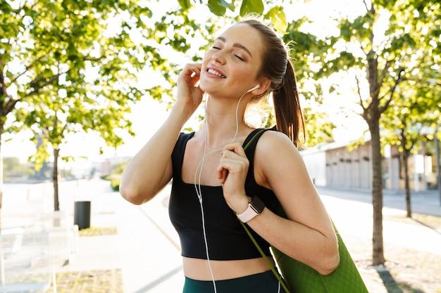 Portret van een jonge sportvrouw die een trainingspak draagt dat naar muziek luistert met oortelefoons en een fitnessmat draagt tijdens een wandeling door het stadspark