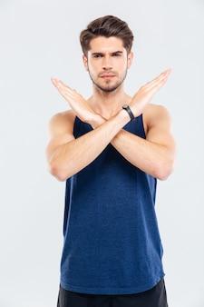 Portret van een jonge sterke man die een stopgebaar toont met gekruiste armen geïsoleerd op een witte achtergrond