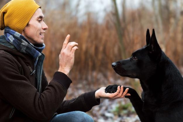 Portret van een jonge stijlvolle blanke man training met grote zwarte hond in de buitenlucht close-up
