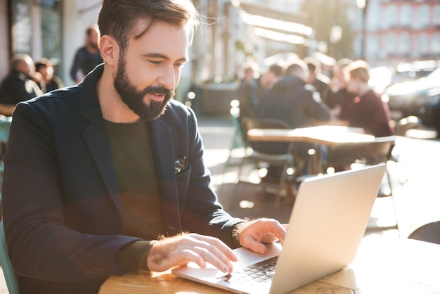 Portret van een jonge stijlvolle man aan het werk op laptopcomputer
