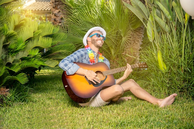 Portret van een jonge stijlvolle spelende en zingende man met gitaar in een tuin