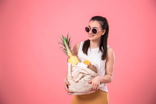 Portret van een jonge stijlvolle vrouw gekleed in zomerkleding en zonnebril, met een eco-fruitzak, op roze geïsoleerd.