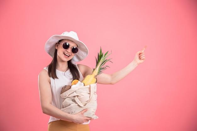Portret van een jonge stijlvolle vrouw gekleed in zomerkleding met een hoed en zonnebril, met een eco-fruitzak, op roze geïsoleerd.