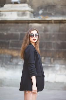 Portret van een jonge stijlvolle vrouw op een straat in de stad